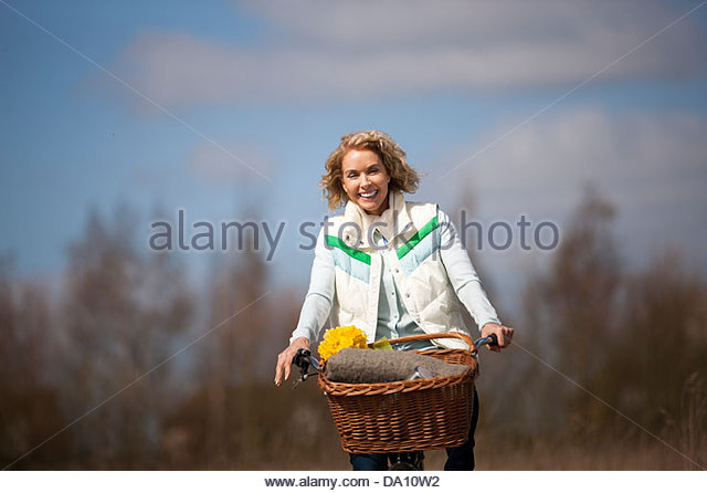 A mature woman cycling along a country path, smiling - Stock Image