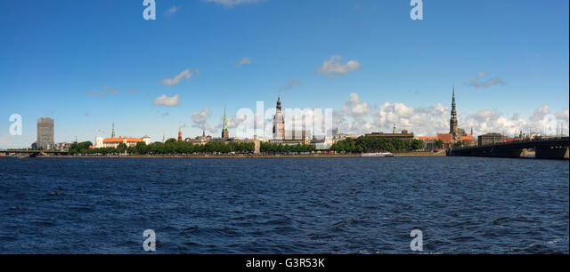 Panorama of Riga with church spiers on the bank of the Daugava river with waves on a background of blue sky with - Stock Image