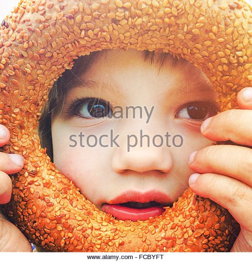Close-Up Of Girl Looking Through Round Bread - Stock Image