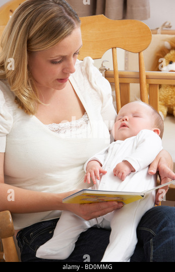 Mother Reading Story To Baby In Nursery - Stock Image