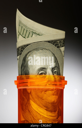 Close up of U.S. dollars in pill bottle - Stock Image
