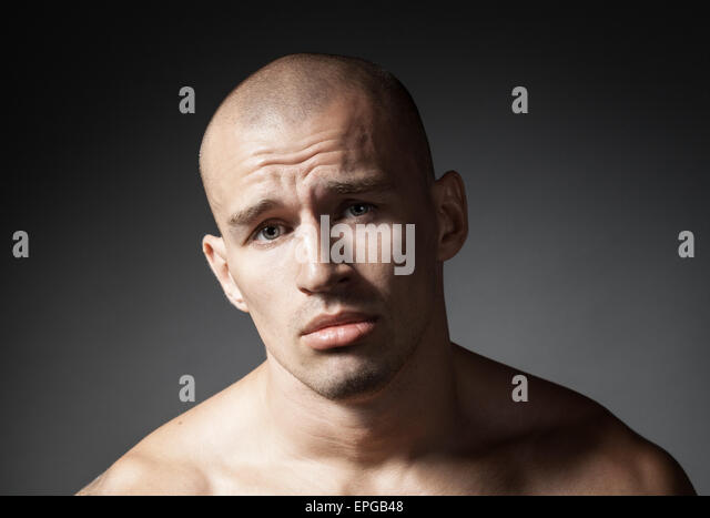 portrait of pitiful strong man isolated on gray - Stock Image