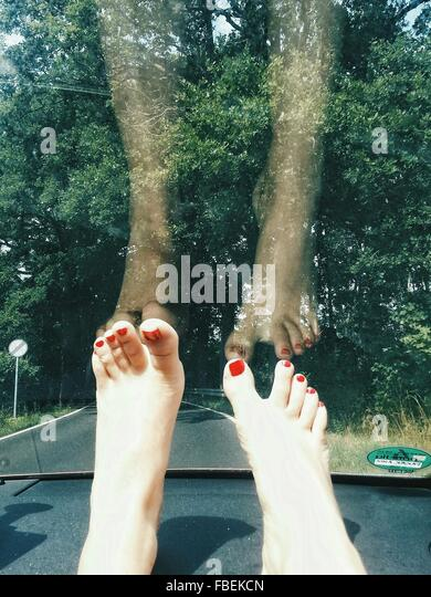 Low Section Of Woman Against Windshield Of Car - Stock Image