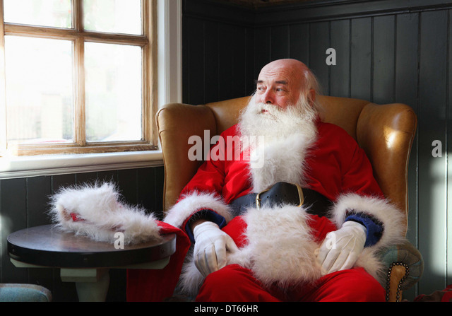 Santa Claus taking break in armchair - Stock-Bilder