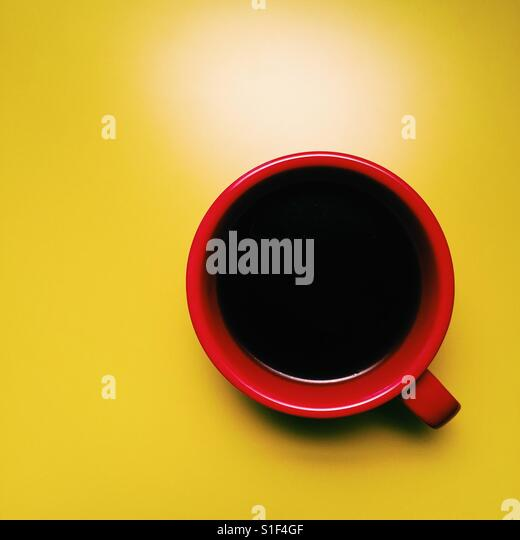 A fresh cup of black coffee on a yellow table - Stock Image