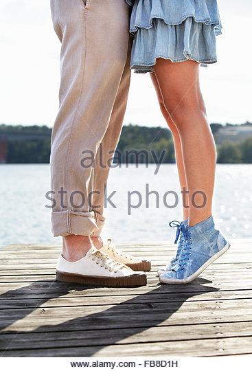Sweden, Uppland, Stockholm Archipelago, Couple standing on pier by lake - Stock Image