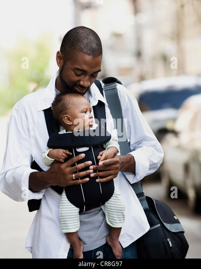 Mid adult man carrying son in baby sling - Stock Image