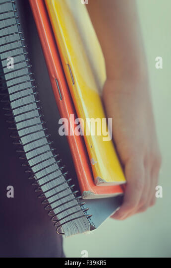 Close-up of a boy holding exercise books - Stock Image