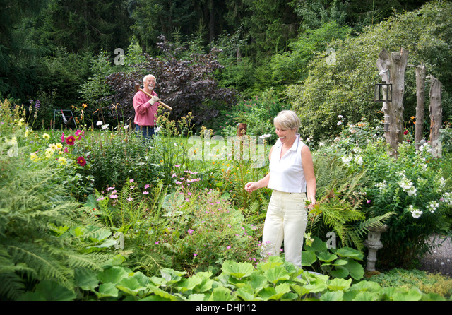 Portrait of senior couple working in garden - Stock Image