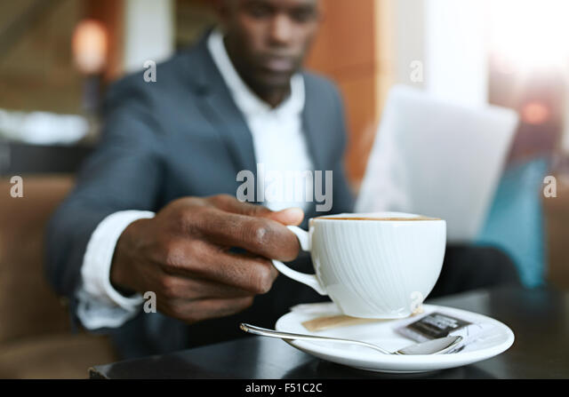 Close up shot of young man 's hand picking up cup of coffee. Businessman sitting at hotel lobby drinking coffee. - Stock Image