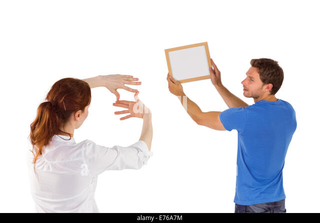Couple deciding to hang picture - Stock Image