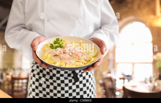 Chef holding dish of salmon pasta - Stock Image