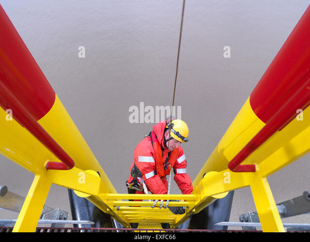 Offshore windfarm worker climbing turbine, high angle view - Stock Image