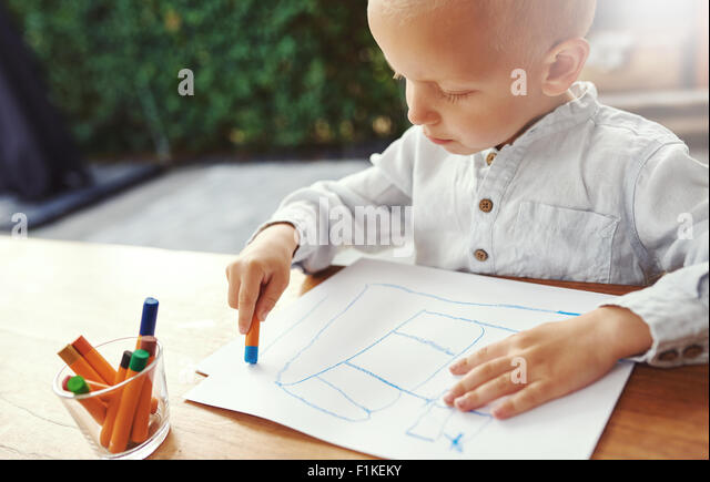 Small boy entertaining himself on a hot summer day standing at a table on an outdoor patio drawing with colored - Stock-Bilder