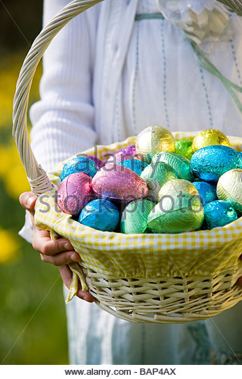 A young girl holding a basket full of Easter eggs - Stock Image