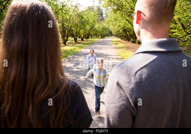 Family of four outdoors in a natural setting with nice light in a lifestyle portrait. - Stock-Bilder