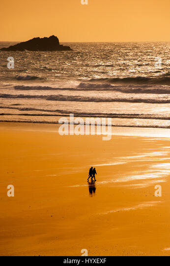 Couple People Silhouette Walking Fistral Beach Sunset Evening Romantic End of the day Shore Shoreline Newquay Cornwall - Stock Image