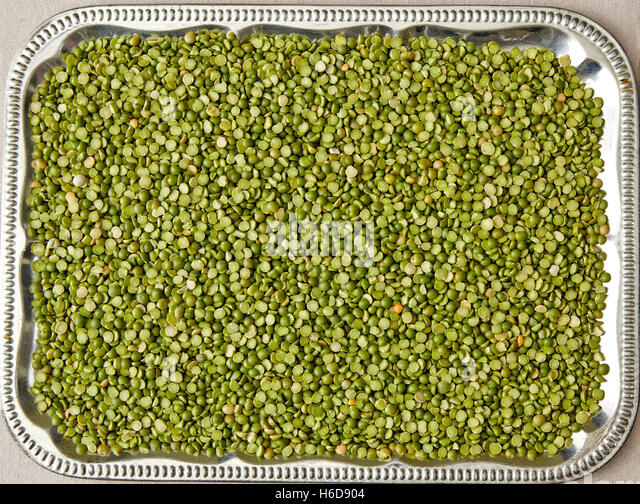 uncooked split peas spread onto a tray - Stock Image