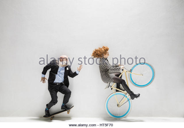 Businessman on skateboard and businesswoman riding bicycle against white background - Stock-Bilder