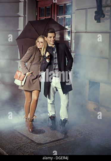 Cute couple with big umbrella - Stock Image