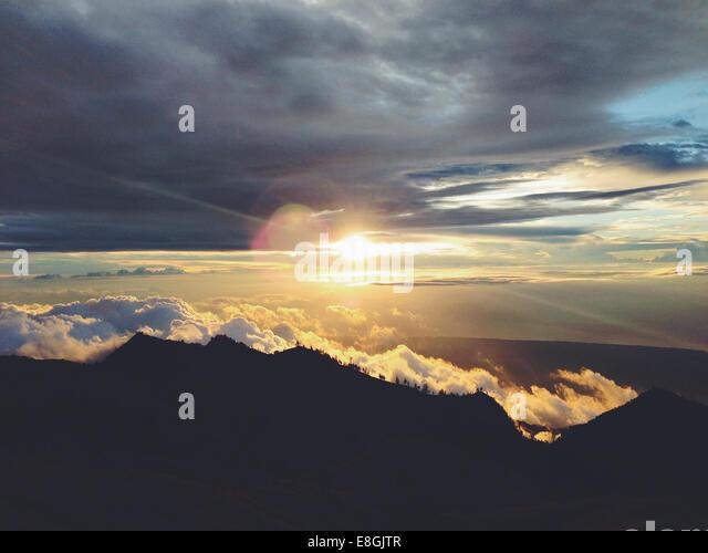 Sun peeping behind clouds - Stock Image