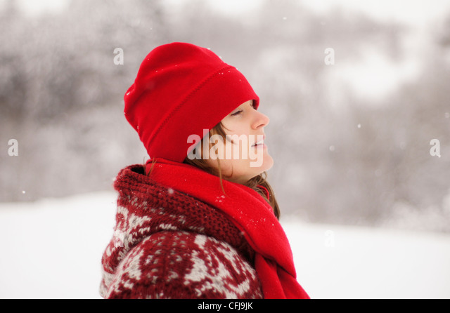Beautiful young girl with red hat and scarf enjoying the falling winter snow - Stock Image
