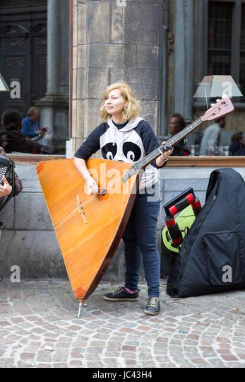A street musician playing the Balalaika in Bruges, Belgium - Stock Image