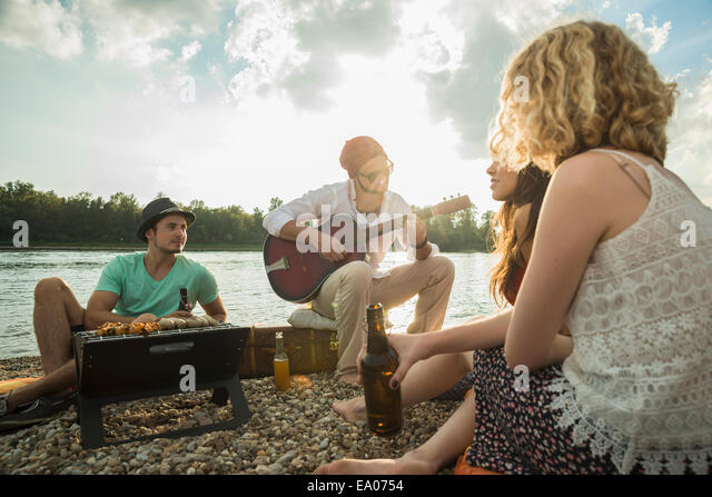 Young man sitting by lake with friends playing guitar - Stock Image