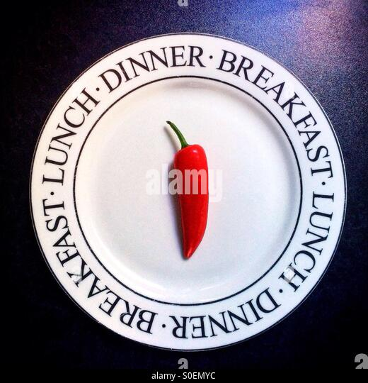 A single red chilli pepper on a white plate decorated with the words breakfast, lunch and dinner. - Stock Image