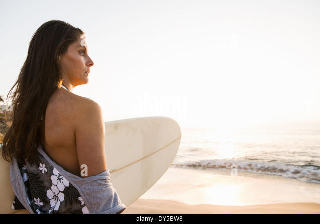 Surfer carrying surf board, looking at sea - Stock-Bilder