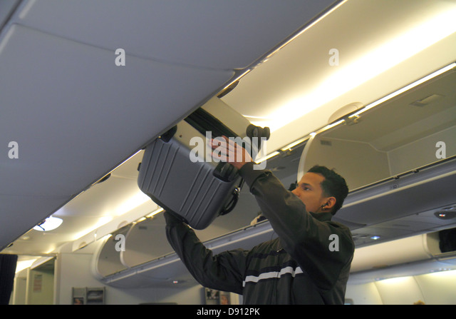 Germany Frankfurt am Main Airport FRA Lufthansa onboard cabin boarding passengers overhead luggage bins Black man - Stock Image