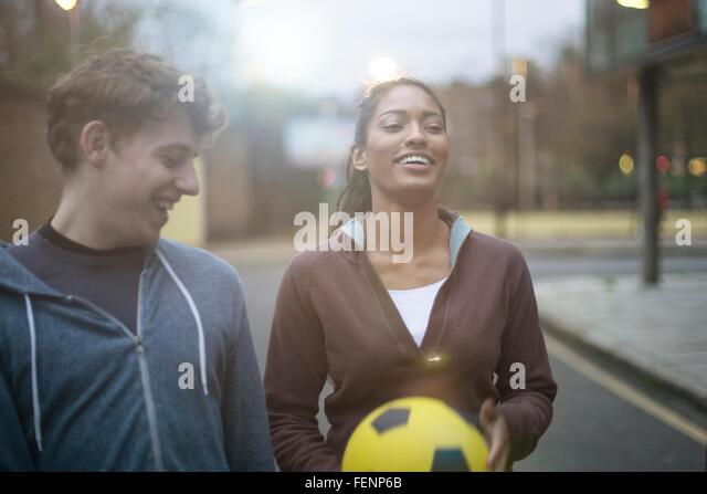 Young man and woman walking in street, holding football - Stock-Bilder