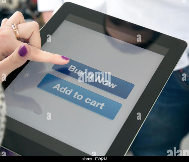 Female fingers clicking on BUY button on the screen of tablet PC - Stock Image