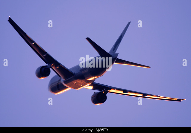 Commercial aeroplane in reflecting sunset light. - Stock Image