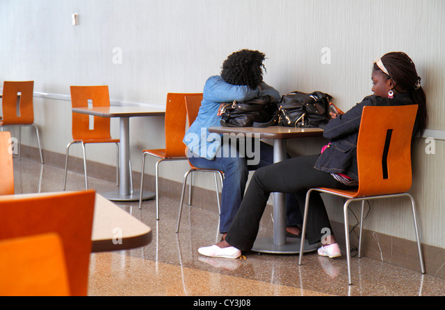 Boston Massachusetts Logan International Airport BOS gate area concourse food court Black woman teen girl waiting - Stock Image