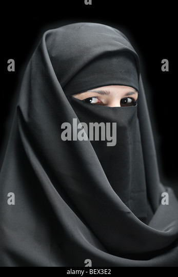 A veiled woman isolated on a black background - Stock Image