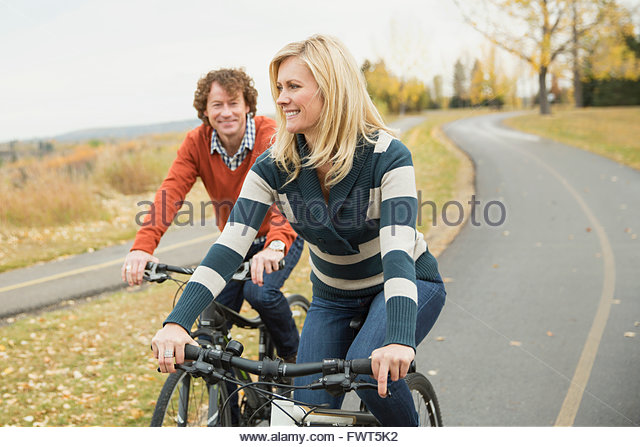 Mature couple riding bicycles on pathway - Stock Image