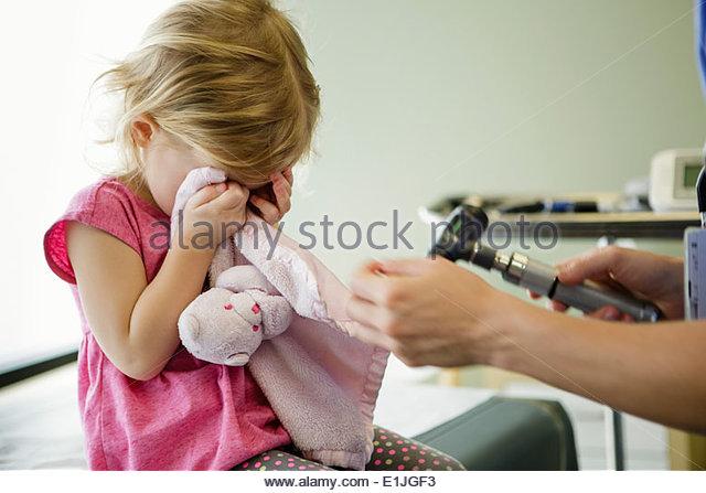 Girl hiding eyes in hospital room - Stock Image