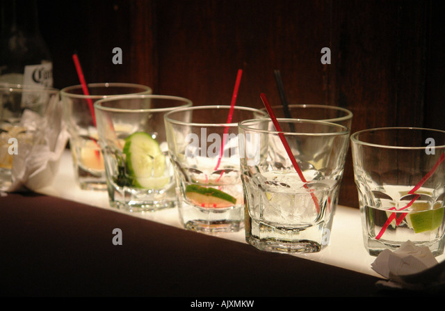 Still Life of Many Beverage Glasses on a Bottom Lit Shelf after a Party - Stock Image