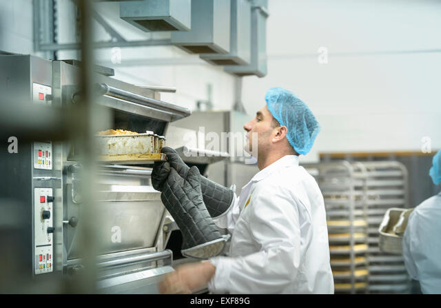 Baker inspecting cakes in oven in cake factory - Stock Image