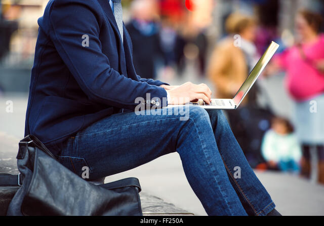 Unrecognizable manager working on laptop on crowded Piccadilly C - Stock Image
