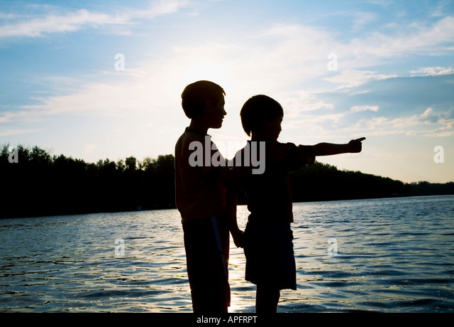 Silhouette of children by a beach - Stock Image