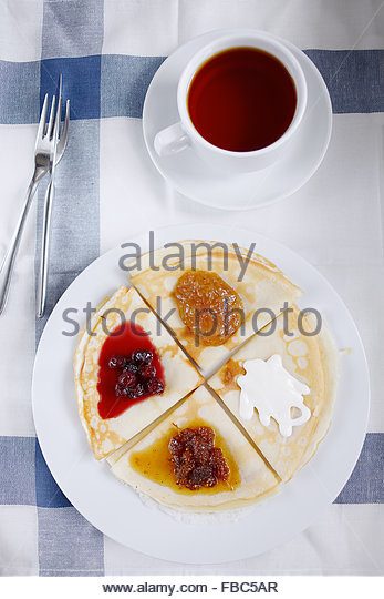 Overhead view of breakfast table setting of berry crepes and black tea - Stock Image