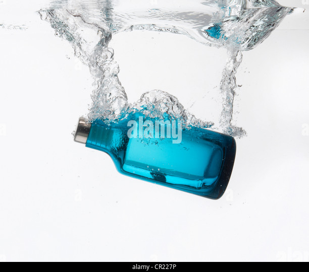 Bottle splashing in water - Stock Image