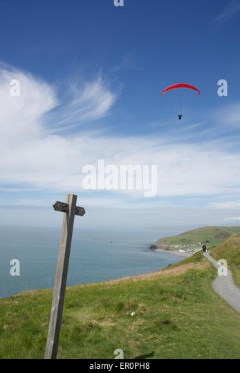A para-glider soars above the Welsh Coastal Path across the top of Constitution Hill in Aberystwyth. - Stock Image