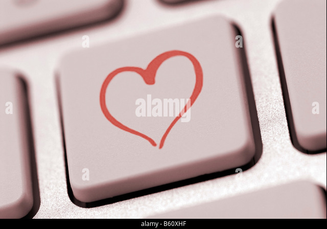 Heart shape on a computer keyboard, symbolic image for internet dating - Stock Image