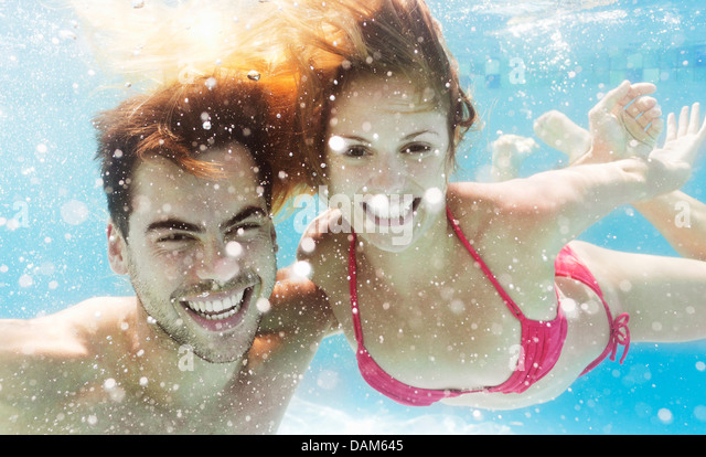 Couple swimming in pool - Stock Image