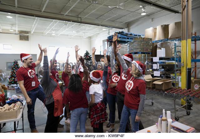 Community volunteers in Santa hats cheering in warehouse - Stock Image