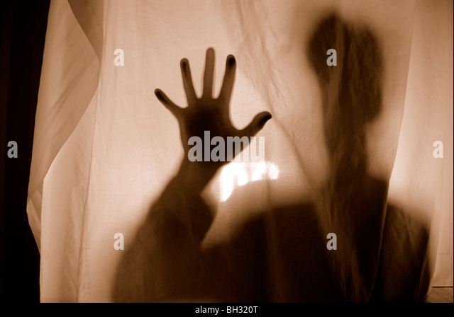 SILHOUETTE BEHIND THIN FABRIC - Stock Image