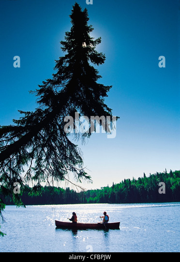 Couple canoeing, Duck Mountain Provincial Park, Manitoba, Canada - Stock Image